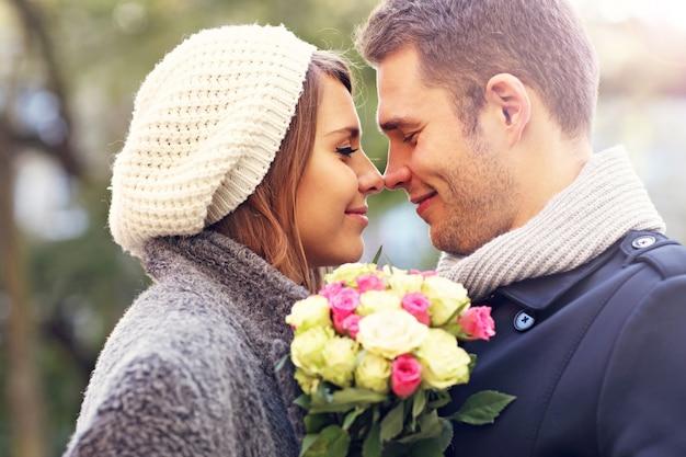 Szczęśliwa para przytulająca się z kwiatami w mieście