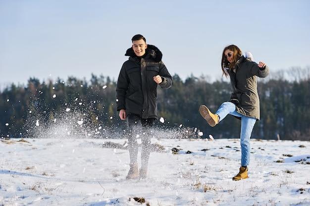 Szczęśliwa para przytulanie i śmiejąc się na zewnątrz w zimie. zdjęcie nadaje się do reklamy odzieży zimowej