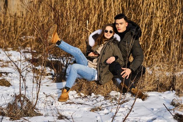 Szczęśliwa para przytulanie i śmiejąc się na zewnątrz w zimie