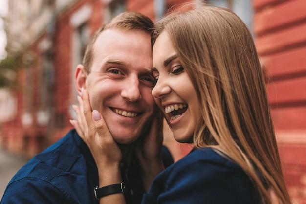 Szczęśliwa para przytulanie i uśmiechając się. portret chłopaka i dziewczyny z uśmiechem na twarzach.