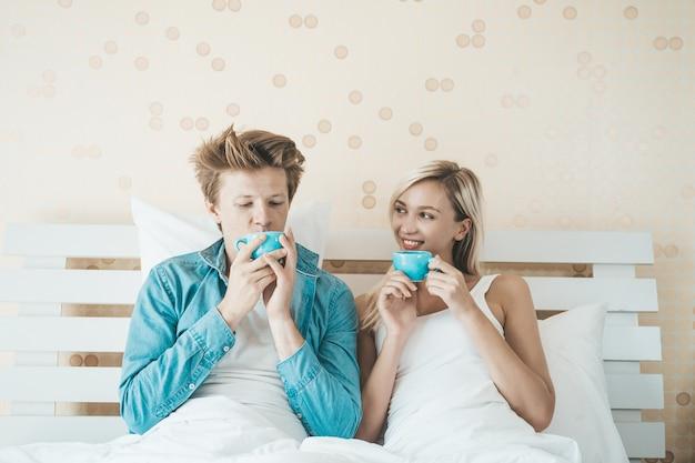 Szczęśliwa para ręka trzyma kubek i picie kawy rano