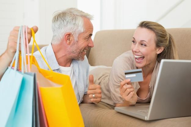 Szczęśliwa para robi zakupy online na leżance