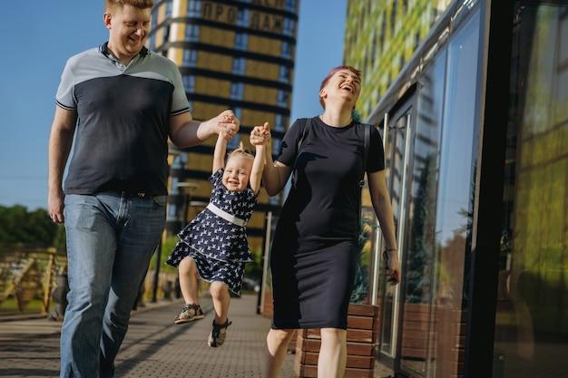 Szczęśliwa para rodzina kaukaski cieszyć spacery z córką. matka radośnie się śmieje. zdjęcie wysokiej jakości