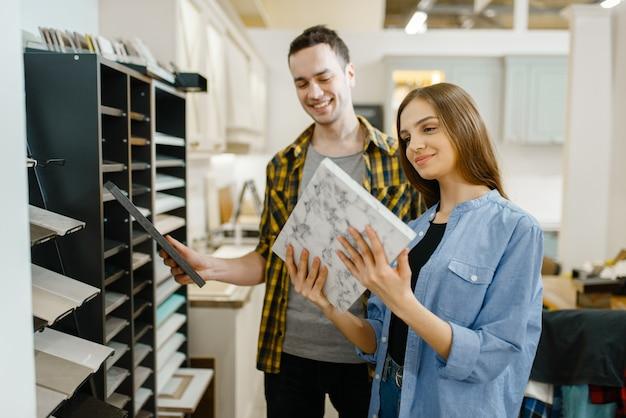Szczęśliwa para rodzina w sklepie meblowym. mężczyzna i kobieta szukający blatu w sklepie, mąż i żona kupują towary do nowoczesnego wnętrza domu