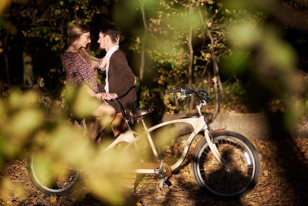 Szczęśliwa para romantyczny, brodaty mężczyzna i atrakcyjna dziewczyna blisko siebie w podwójnym rowerze tandem