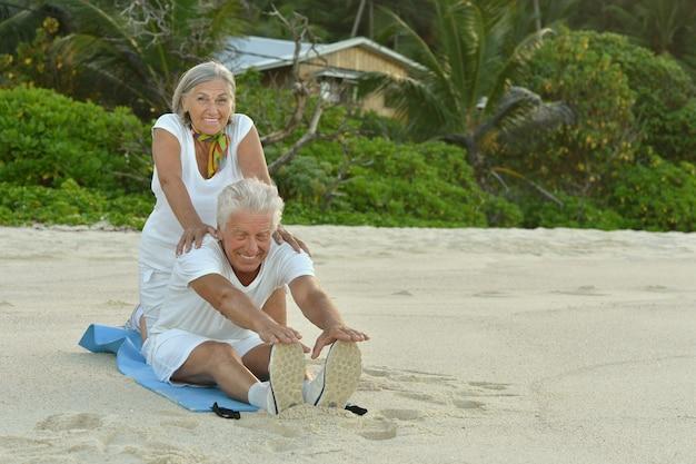 Szczęśliwa para seniorów ćwiczących latem nad brzegiem morza