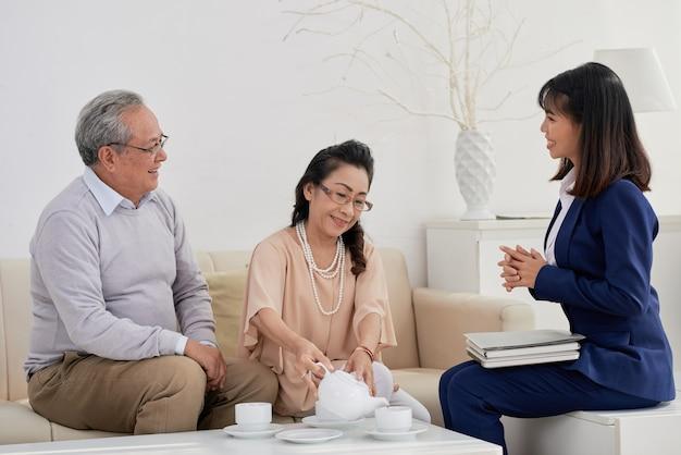 Szczęśliwa para seniorów i zarządca nieruchomości piją herbatę i rozmawiają o zainteresowaniach i preferencjach