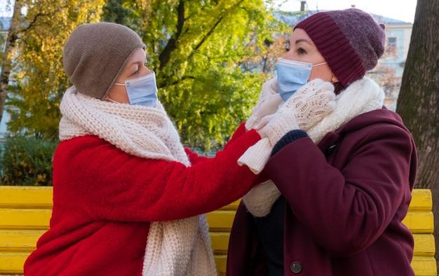 Szczęśliwa para seniorów lub kobiety w średnim wieku mają na sobie ochronną maskę medyczną i siedzą na ławce w jesiennym parku.