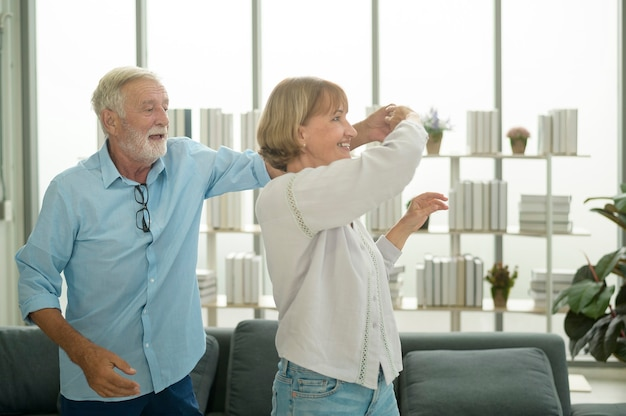 Szczęśliwa para seniorów rasy kaukaskiej tańczy w domu