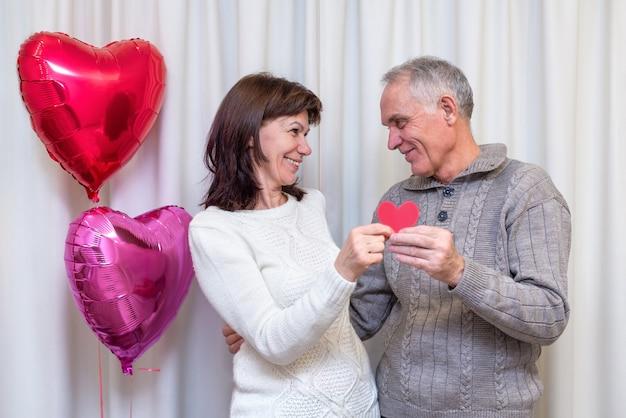 Szczęśliwa para seniorów świętuje walentynki. mężczyzna i kobieta trzymają czerwone serce w dłoniach i uśmiech