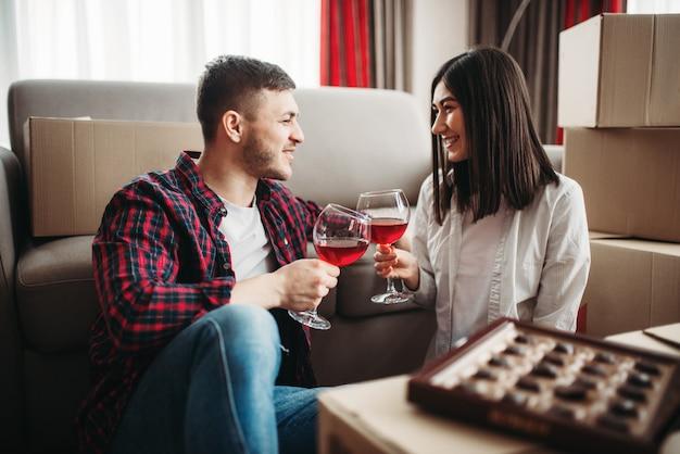 Szczęśliwa para siedzi między kartonami i świętuje przeprowadzkę do nowego domu. r