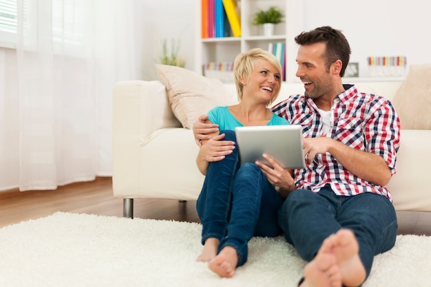 Szczęśliwa para siedzi na dywanie w domu i za pomocą cyfrowego tabletu