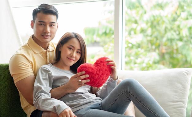Szczęśliwa para siedzi na kanapie i jest mężczyzną, obejmując swoją dziewczynę