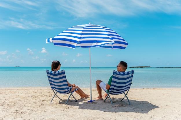 Szczęśliwa para siedzi na krzesłach pod parasolem na tropikalnej plaży. koncepcja wakacji letnich.