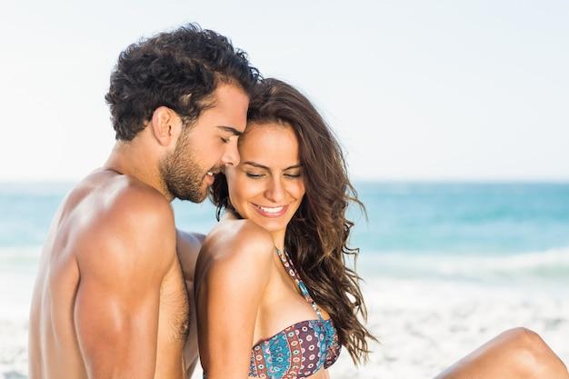 Szczęśliwa para siedzi na plaży