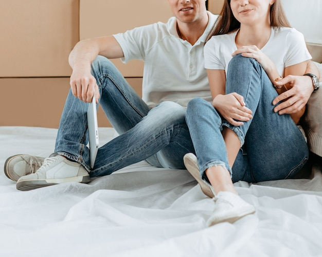 Szczęśliwa para siedzi obok pudeł w nowym mieszkaniu. zdjęcie z miejsca na kopię