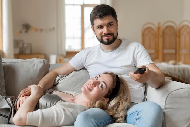 Szczęśliwa para siedzi razem na kanapie
