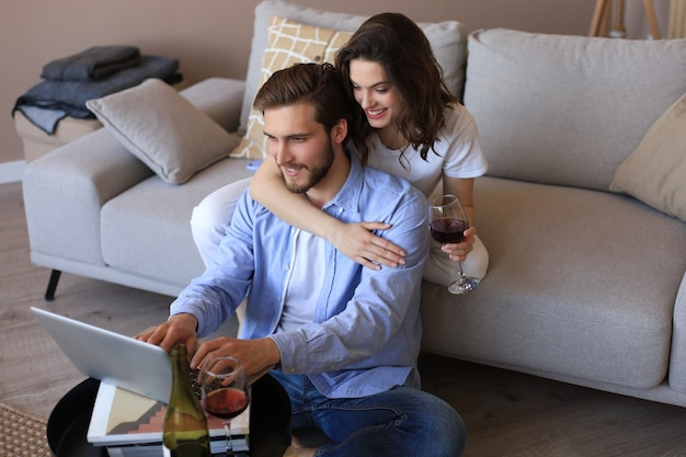 Szczęśliwa para siedzi, relaksuje się na podłodze w salonie, używając laptopa do wspólnych zakupów online, oglądając film, pijąc czerwone wino.