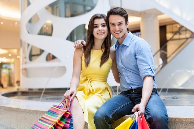 Szczęśliwa para siedzi w centrum handlowym obok fontanny