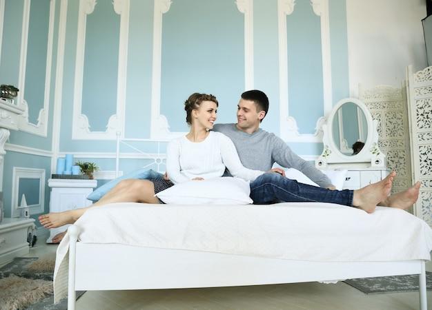 Szczęśliwa para siedzi w łóżku w przestronnej sypialni i patrzy na siebie