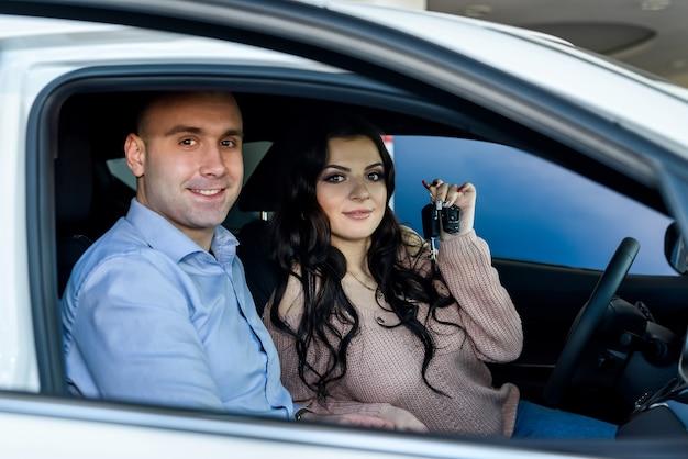 Szczęśliwa para siedzi w nowym samochodzie i uśmiecha się w salonie