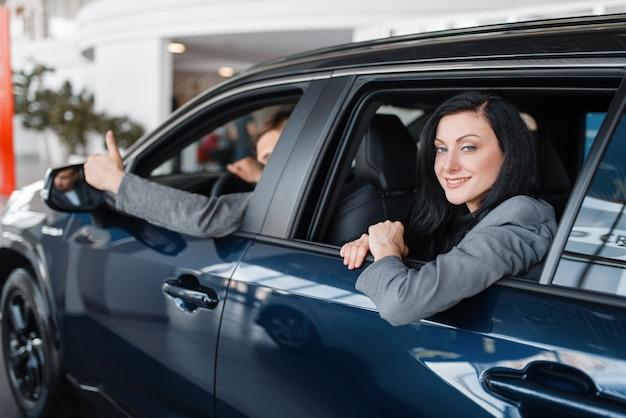 Szczęśliwa para siedzi w nowym samochodzie