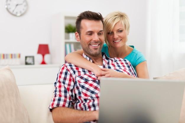 Szczęśliwa para siedzi w salonie i za pomocą laptopa