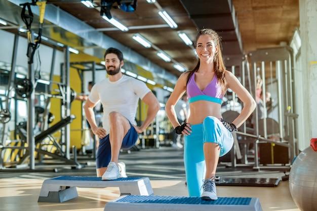 Szczęśliwa para silnych ćwiczeń na siłowni. używanie steppera do treningu.