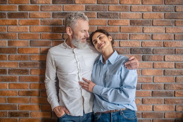 Szczęśliwa Para. Siwowłosy Mężczyzna Przytulający Swoją żonę Stojąc Przy Ceglanym Murze Premium Zdjęcia