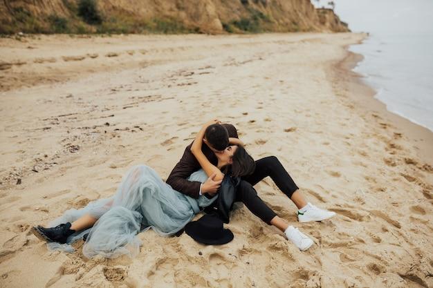 Szczęśliwa para ślub leży na piaszczystej plaży w pobliżu morza i całuje.