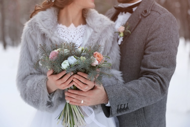 Szczęśliwa para ślub z bukietem na zewnątrz w zimowy dzień, zbliżenie
