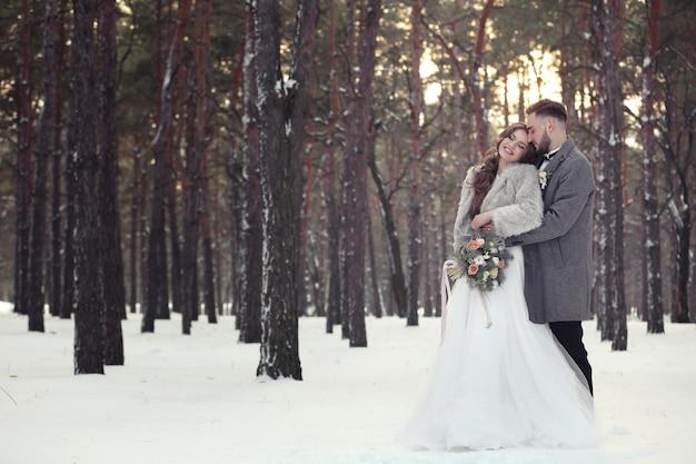 Szczęśliwa para ślubna na zewnątrz w zimowy dzień