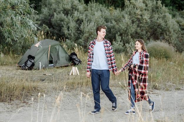 Szczęśliwa para spaceru trzymając rękę na tle namiotu i ogniska w przyrodzie