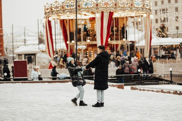 Szczęśliwa para spaceruje po parku rozrywki w zimie