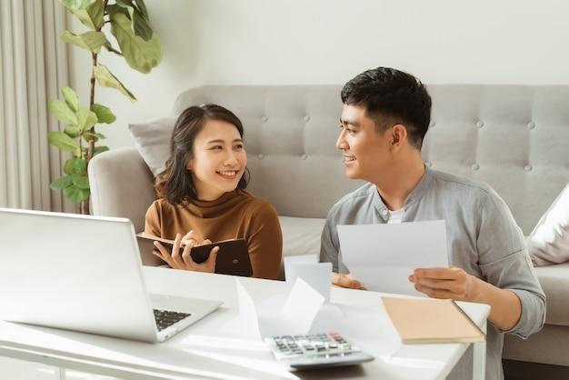 Szczęśliwa para spędza czas razem w domu z laptopem