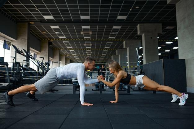 Szczęśliwa para sportowa robi pompki, trenuje w siłowni
