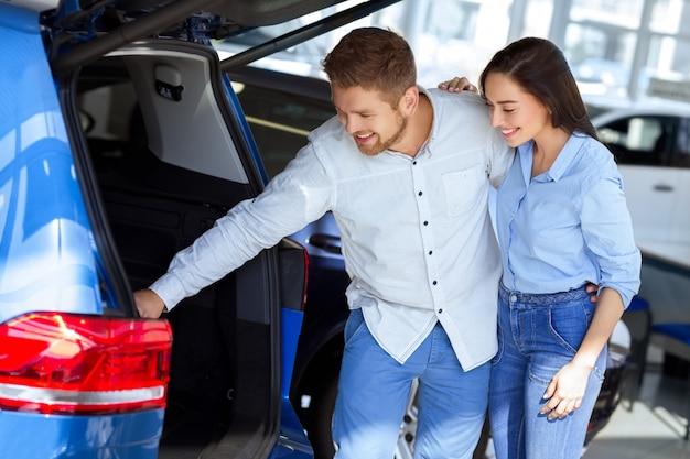 Szczęśliwa para sprawdzanie bagażnika nowego samochodu w salonie