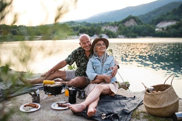 Szczęśliwa para starszy odpoczynek na letnie wakacje, grill nad jeziorem.