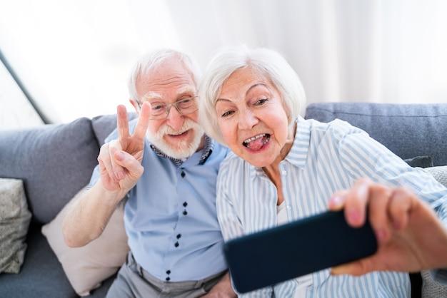 Szczęśliwa para starszych bawi się i robi zdjęcie na telefonie komórkowym, aby udostępnić online