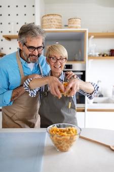 Szczęśliwa para starszych bawiących się, gotujących w domowej kuchni