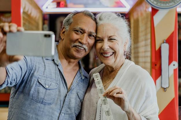 Szczęśliwa para starszych biorąca selfie z biletami na loterię