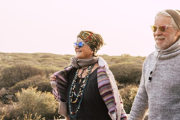 Szczęśliwa para starszych emerytów w ciepłej odzieży korzystających z pieszej wycieczki. aktywna para starszych spacerująca razem i podziwiająca malowniczy widok podczas wakacji. stylowa para seniorów podróżująca na świeżym powietrzu