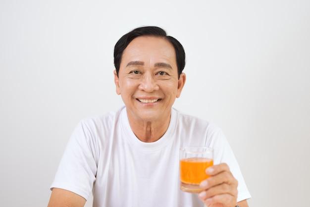 Szczęśliwa para starszych jedząca śniadanie rogalika w domu i pijąca sok pomarańczowy