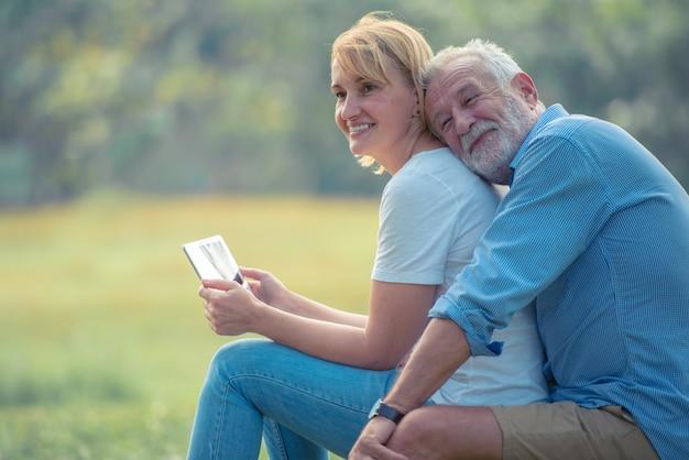 Szczęśliwa para starszych korzystających spędzać czas razem, przytulanie, rozmawiając z uśmiechniętą twarzą i śmiejąc się