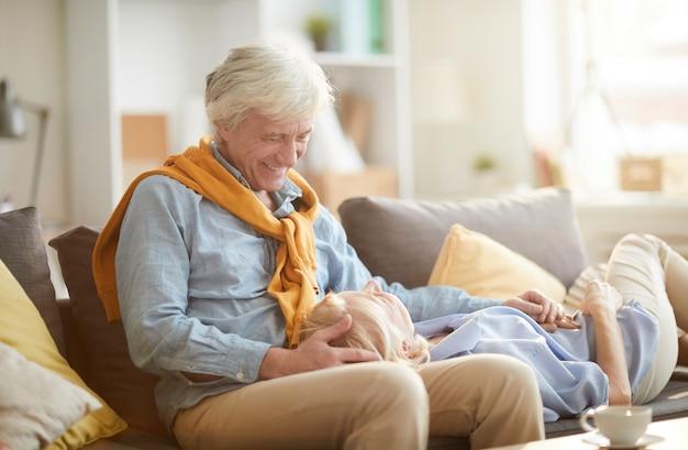 Szczęśliwa para starszych, leżąc na kanapie