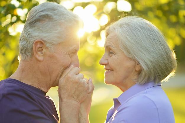 Szczęśliwa para starszych, mężczyzna całuje kobietę w rękę o przyrodę na tle zachodu słońca