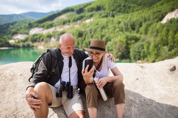 Szczęśliwa para starszych na pieszej wycieczce na letnie wakacje, robiąc miny podczas robienia selfie.