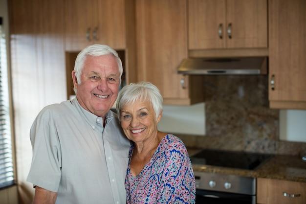 Szczęśliwa para starszych obejmując siebie w kuchni w domu