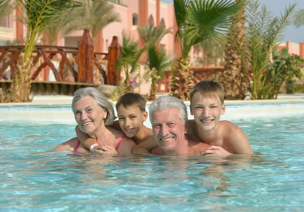 Szczęśliwa para starszych odpoczywa na basenie razem z wnukami