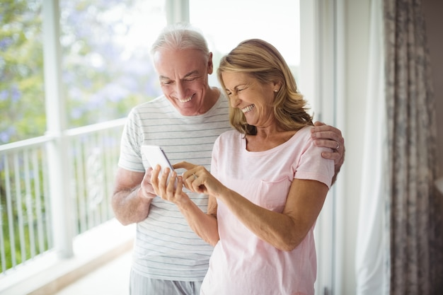 Szczęśliwa para starszych przy użyciu telefonu komórkowego na balkonie